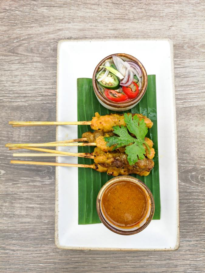 Thailändska satay fega steknålar med jordnötsås på plattan som täckas av bananbladet royaltyfri bild