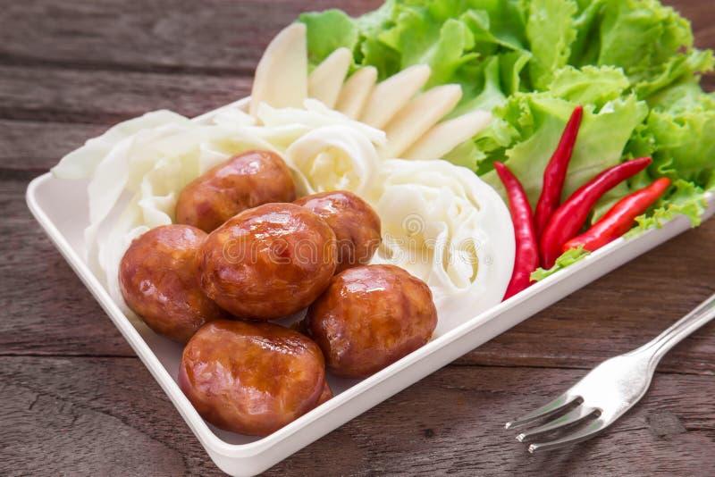 Thailändska stilkorvar och nya grönsaker på maträtten, thailändsk mat arkivbild