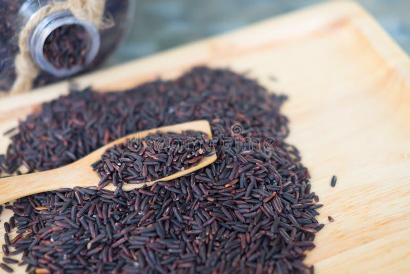Thailändska svarta jasminris i träsked royaltyfri bild
