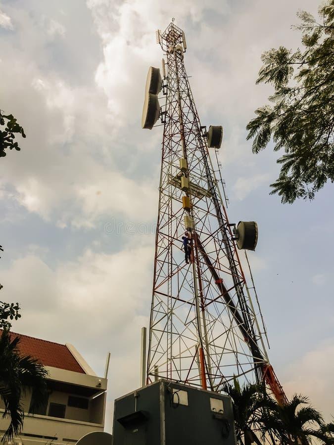 Thailändska tekniker som arbetar på ett telekommunikationtorn i Pattaya royaltyfri fotografi