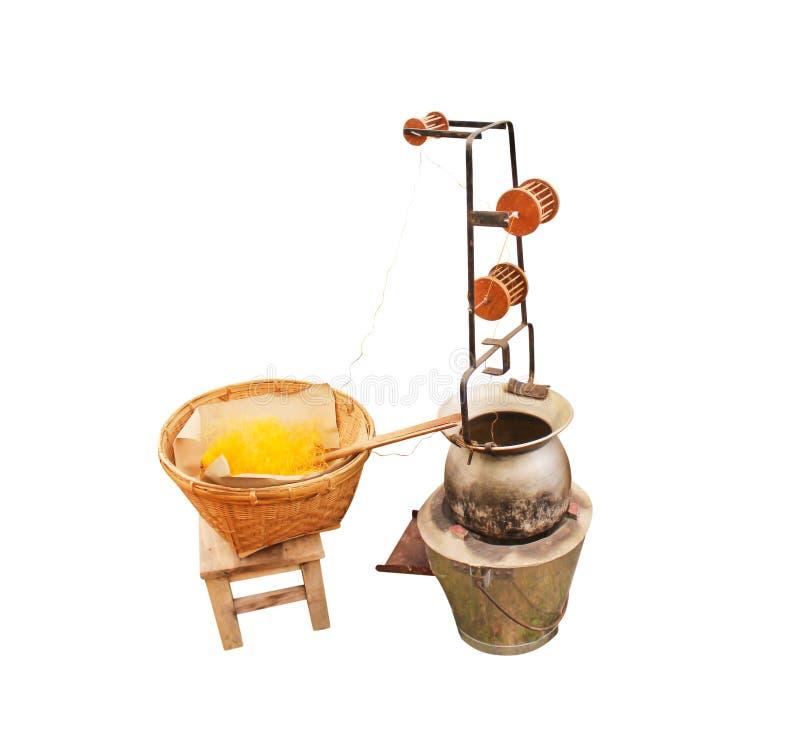 Thailändska traditionella moment av silke som reeling, genom att koka guld- silkesmaskkokonger i kruka på kolugnen och träutrustn royaltyfri foto
