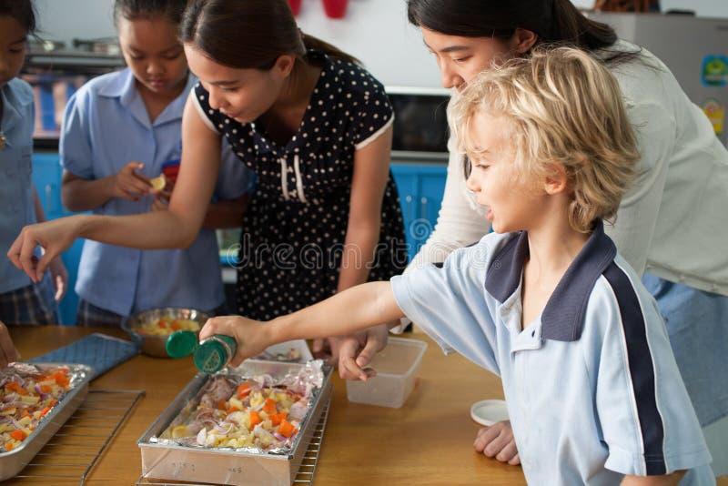 Thailändska unga skolbarn tar en matlagninggrupp royaltyfri fotografi