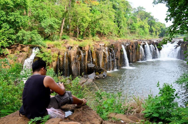 Thailändskt fett mansammanträde och kopplar av på stenen på den Tad Pha Suam vattenfallet arkivbilder