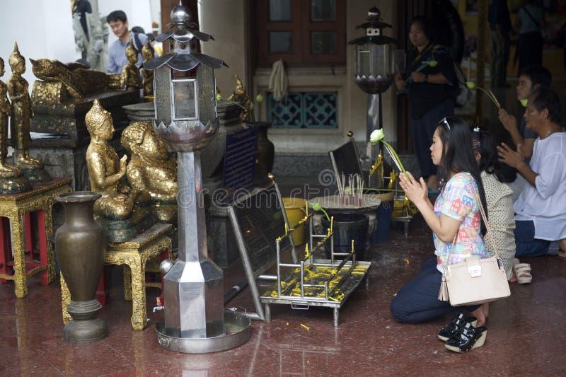 Thailändskt folk som ber på den buddistiska relikskrin i Bangkok royaltyfria bilder