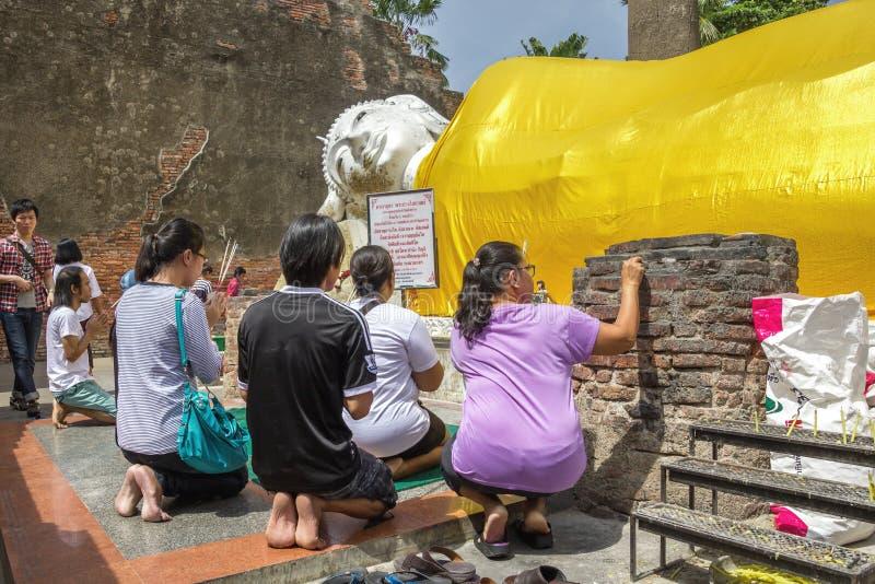 Thailändskt folk som ber till statyn för vila buddha på Wat Yai Chaimongkol i Ayutthaya, Thailand arkivbilder