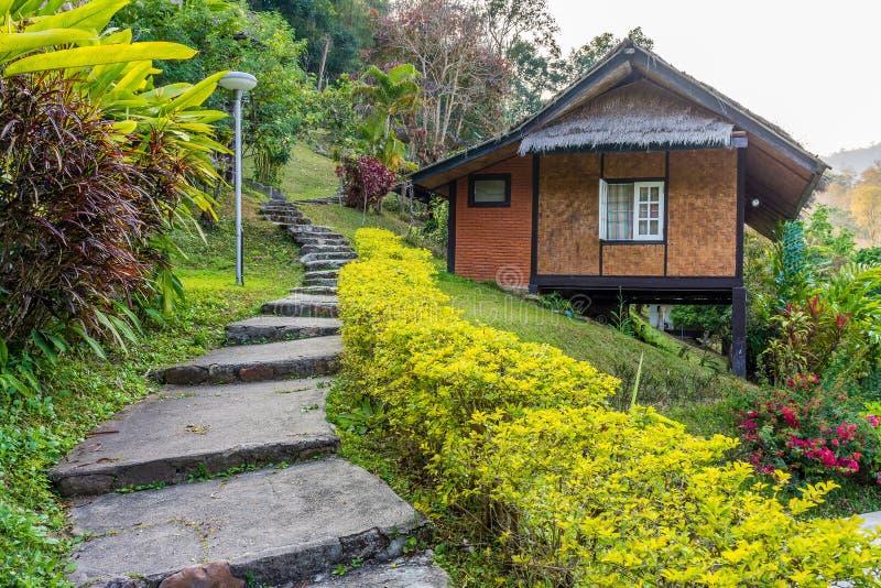 Thailändskt hem för tappning och betonggångbana i trädgård royaltyfria foton