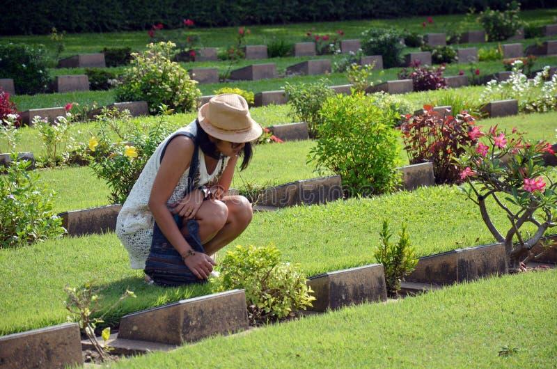 Thailändskt kvinnaläsningord på kyrkogården för gravstenKanchanaburi krig (Don Rak) arkivfoto