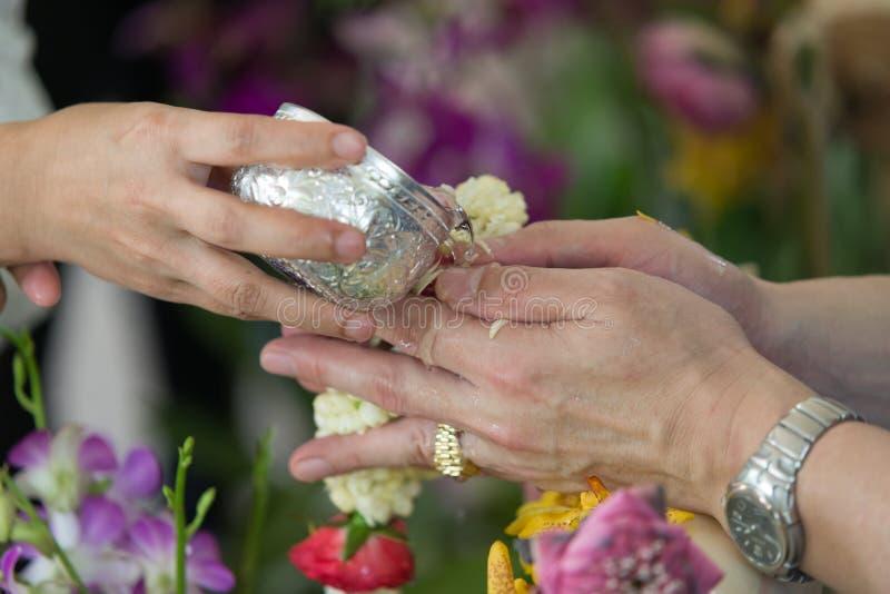 Thailändskt nytt år - ungdomarsom häller vatten och blommor på händerna av pensionären i Songkran ceremoni arkivbilder