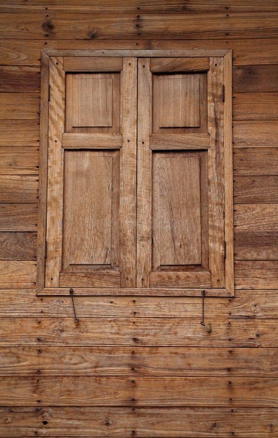 Thailändskt stilhus med den wood fönster och väggen för teakträ arkivbilder
