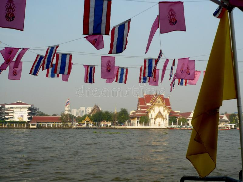 The Chao Phraya River Life Blood of Old and New Bangkok. Thail Flags waving over the Chao Phraya River which is the life blood of the old and new Bangkok stock images