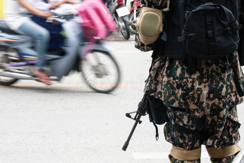 Thail?ndische Armee mit Gewehr in seiner Hand w?hrend der Sicherheitspatrouille nahe einem lokalen Markt in Narathiwat, S?d-Thail lizenzfreie stockbilder