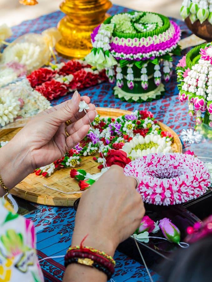 Thail?ndische Frau, die eine Tradition thail?ndische Blumengirlande herstellt stockbild
