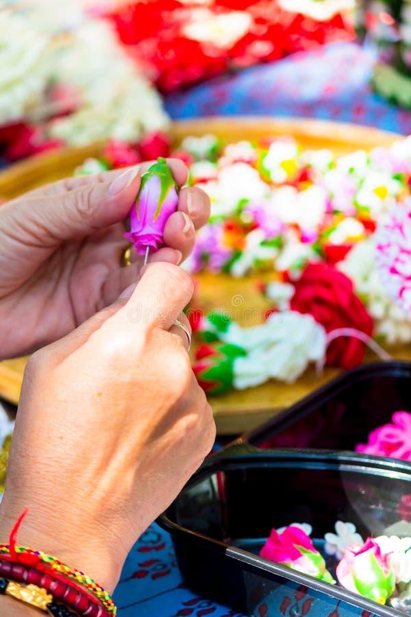 Thail?ndische Frau, die eine Tradition thail?ndische Blumengirlande herstellt stockbilder