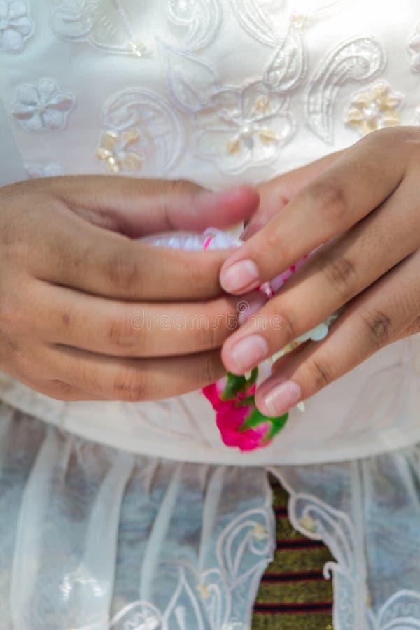 Thail?ndische Frau, die eine Tradition thail?ndische Blumengirlande herstellt stockfotografie