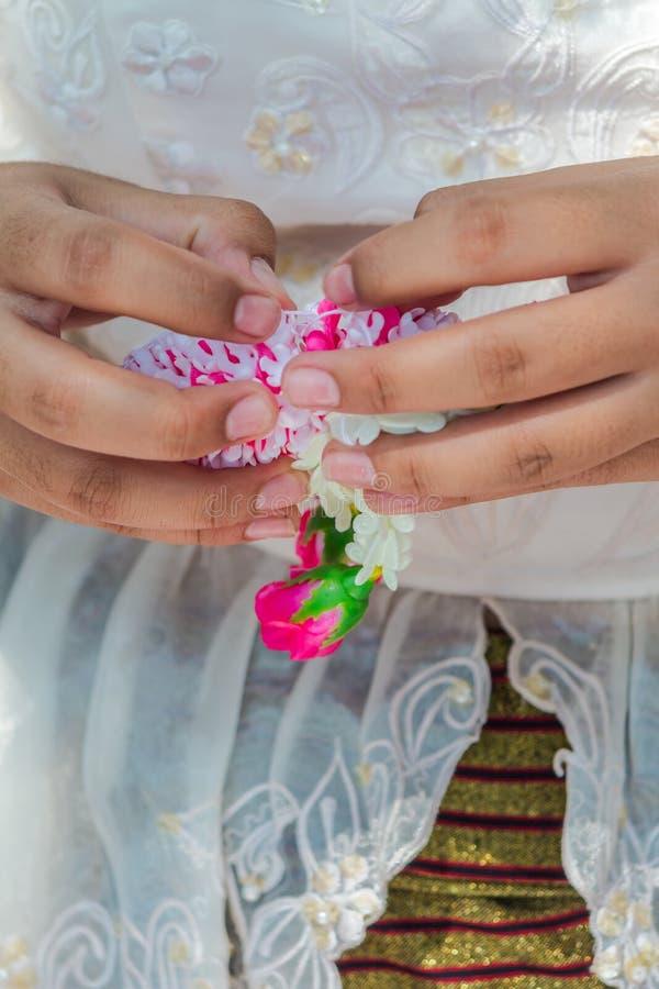 Thail?ndische Frau, die eine Tradition thail?ndische Blumengirlande herstellt lizenzfreies stockfoto