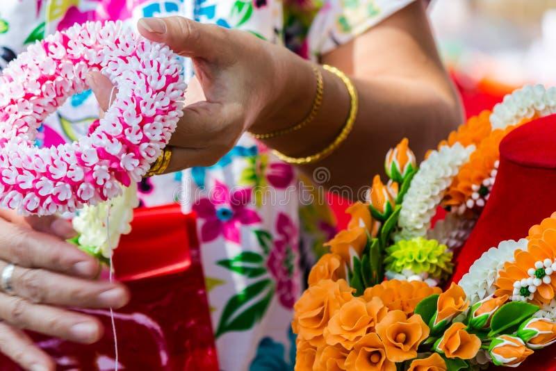 Thail?ndische Frau, die eine Tradition thail?ndische Blumengirlande herstellt lizenzfreie stockfotografie