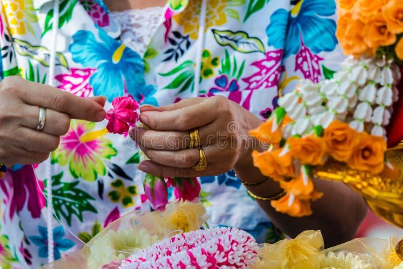 Thail?ndische Frau, die eine Tradition thail?ndische Blumengirlande herstellt lizenzfreie stockbilder