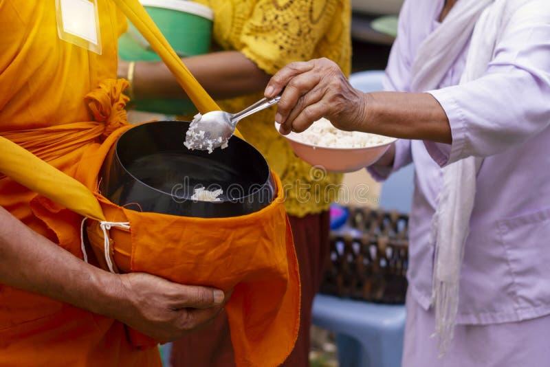 Thail?ndische Leute legen Lebensmittel einem M?nch vor, ` s, das Almosen am Ende von buddhistischem Lent Day rollen lizenzfreie stockfotos