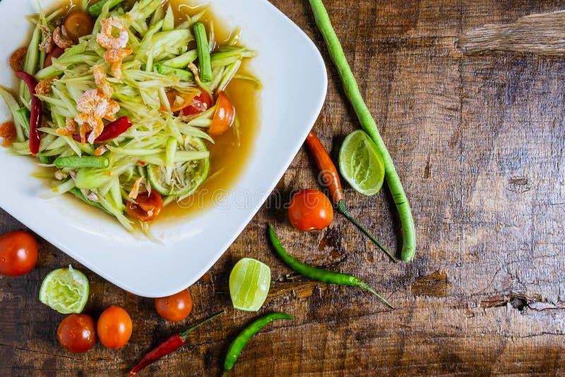 Thail?ndsk mat, papayasallad och tomater, peppar och smaktillsatser p? en tr?tabell royaltyfria bilder