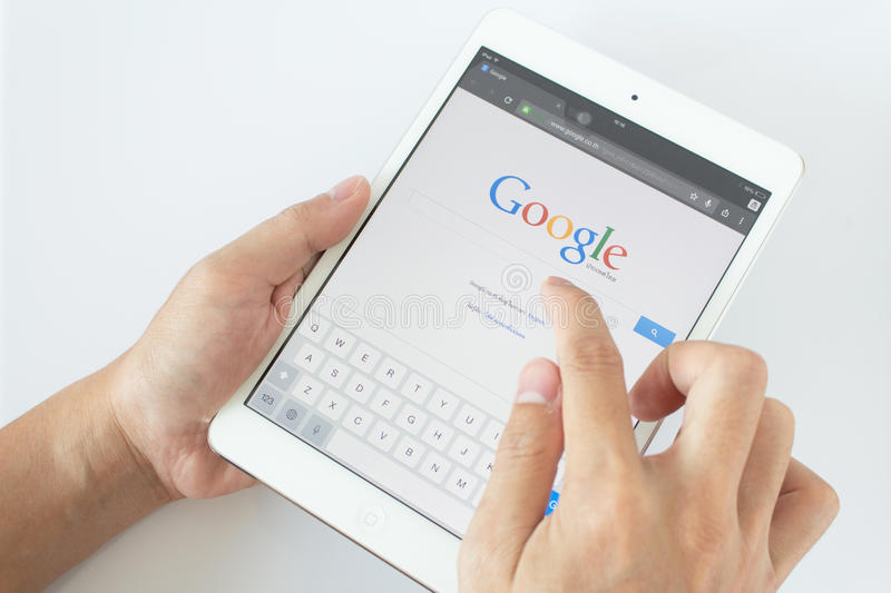 Thailand - April 6: Man hands are pointing on touch screen device with google serch.Google serch is top in serch engine in royalty free stock photo