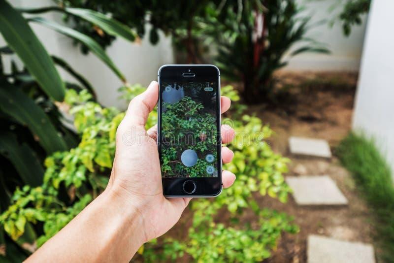 THAILAND - 6 augustus - Aziatisch van de holdingsapple van de kerelhand iphonese, het spelen Pokemon gaat toepassing op het scher stock foto's