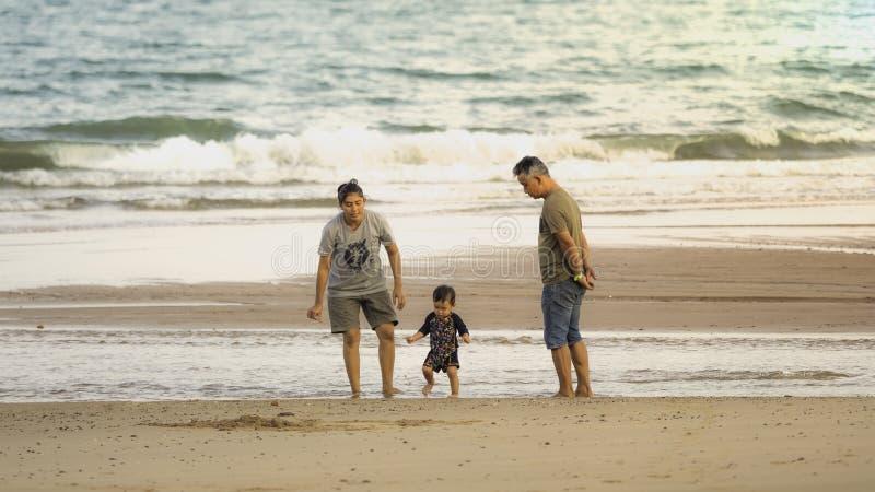 Thailand at Bang saphan noi Bangburd beach. on 27/04/2019. Happy family - father, mother, baby son run and play sea water and yell stock images