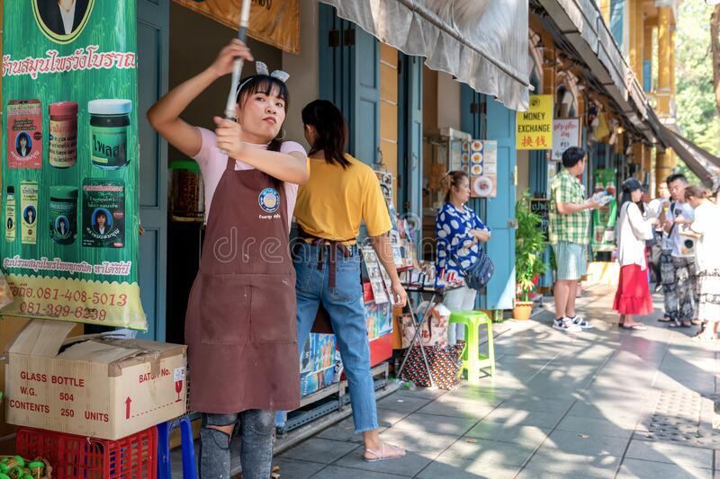 Thailand, Bangkok, February 1, 2019: Asian Thai girl in an apron seller and cook, closes the street shop and dining room. Street stock photos