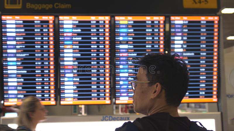 Thailand Bangkok, 29 januari 2018 Man passageraren som ankommer och ser schemat för flygbagagereklamationen i flygplatsen royaltyfri foto