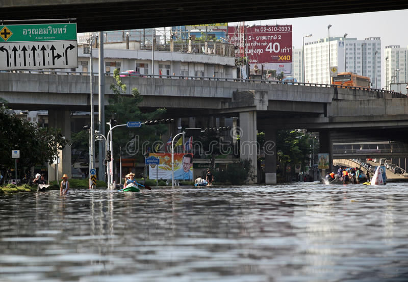 Thailand, Bangkok - November 2011: local residents moving on the water flooded the streets of the city during the flooding in Bang royalty free stock photography