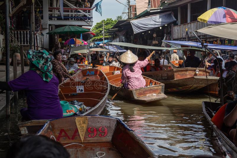 Thailand, Bangkok - 06 November 2018: Tourists in traditional wooden boat buying goods on Damnoen Saduak Floating Market.  royalty free stock photos