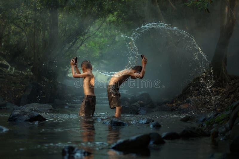 Thailand de jongens die waterplons op de kreek met vrienden spelen stock afbeelding