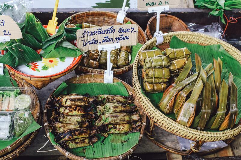 Thailand floating market.Row of grilled coconut sticky rice with varieties of filling stock photo