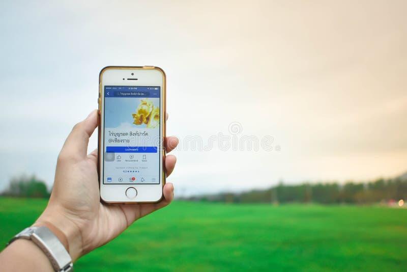 Thailand - 11 Juli 2018: Smartphone van de handholding toont vertoning van Facebook-Toepassing en mening van landschap op de acht stock afbeeldingen
