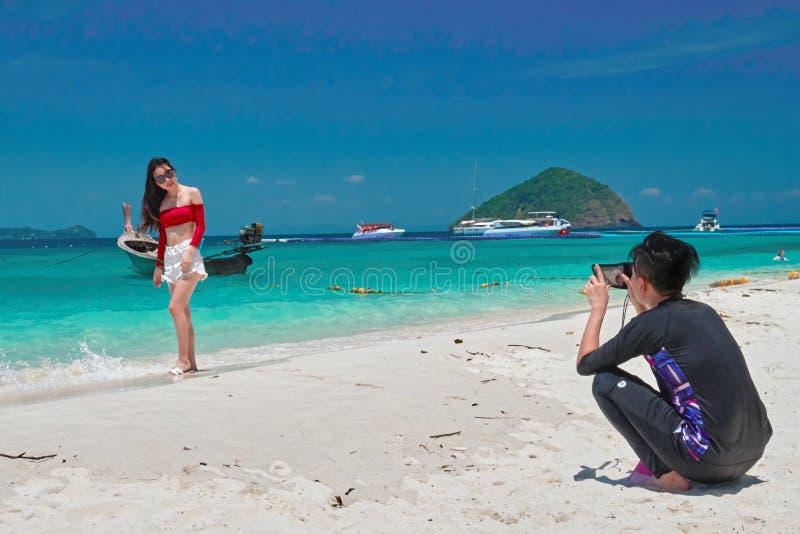 THAILAND, KORAALeiland, 19 MAART, 2018 - het Chinese meisje van jonge mensenfoto's in een rode blouse op het strand tegen het tro stock fotografie