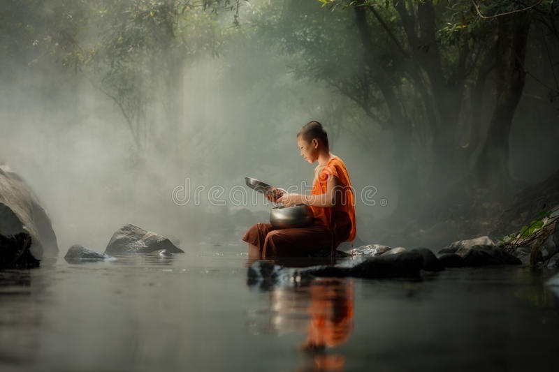 Thailand Little monk sitting on the creek or river in forest at. Countryside Thailand of Buddhism, Southeast asia royalty free stock images