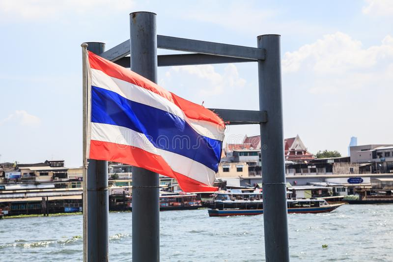 Thailand National Flag at boat pier with beautiful summer view of Thai riverside naval commuter traffic background in Chao Phraya royalty free stock image