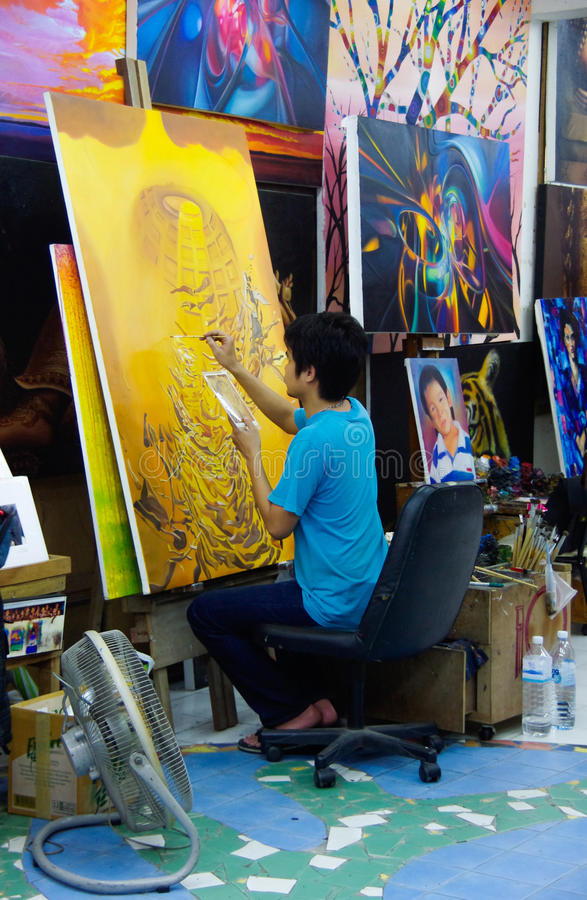 Thailand: painter paints studio yellow. Thailand: painter paints a picture in a indoor studio stock image