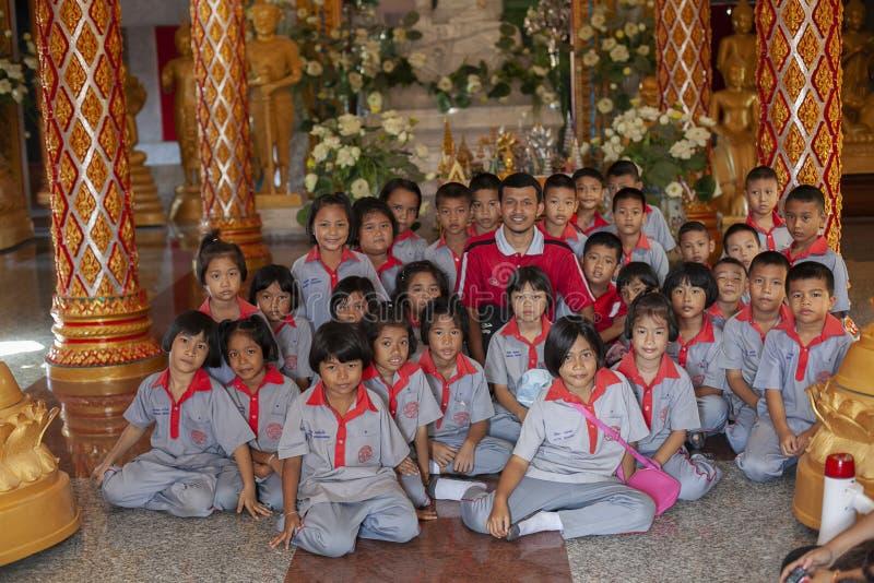 Thailand, Phuket, 01 18 2013 Basisschoolstudenten en een leraar in de tempel van Boedha, groepsfoto Onderwijs Opleiding royalty-vrije stock afbeeldingen