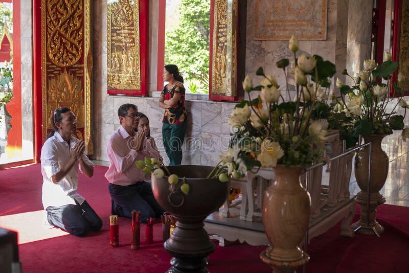 Thailand, Phuket, 01 18 2013 Een mens en zijn familie bidden in een Boeddhistische tempel in de ochtend Het concept godsdienst royalty-vrije stock foto