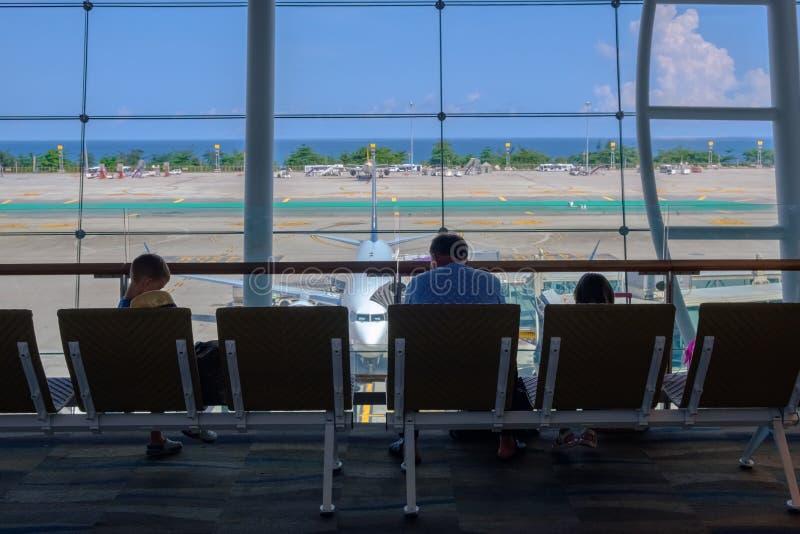 Thailand Phuket - 09 05 18 Familj, man och ungar som sitter och väntar tillsammans i flygplatsen för avvikelse arkivbilder