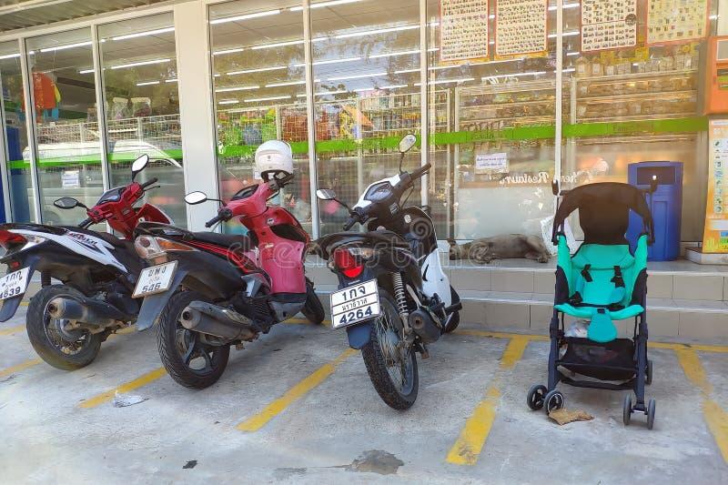 Thailand, Phuket - 23. Februar 2019: Motorradparken und ein Kinderwagen in einem Parkplatz vor dem Speicher Babyfahrten stockfoto
