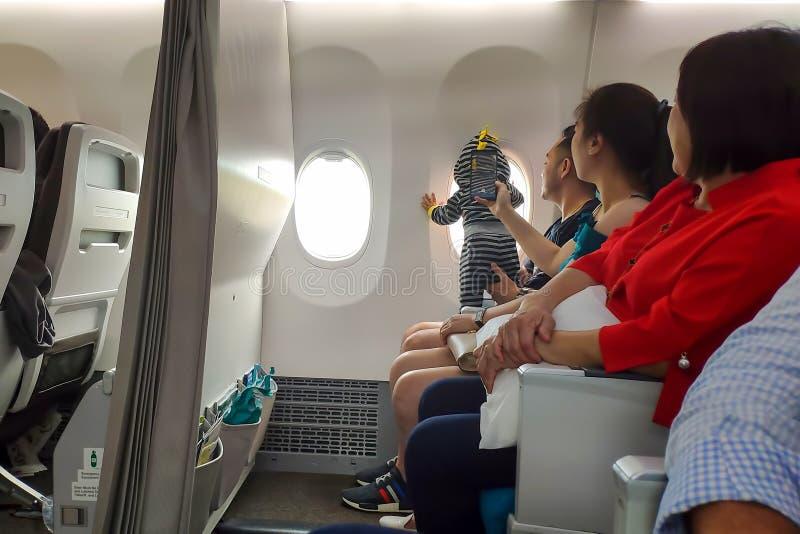 Thailand, Phuket - Februari 27, 2019: Jonge Aziatische familie op het vliegtuig met een kind van de zuigelings klein baby dat uit royalty-vrije stock afbeeldingen