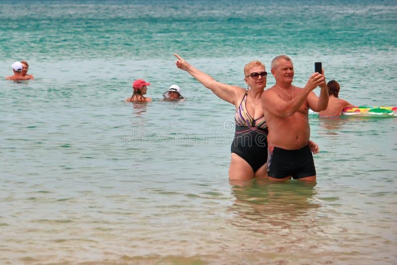 THAILAND, PHUKET, 23 MAART, 2018 - het Bejaarde paar, de man en de vrouw nemen selfie tegen het tropische overzees De ruimte van  stock afbeelding