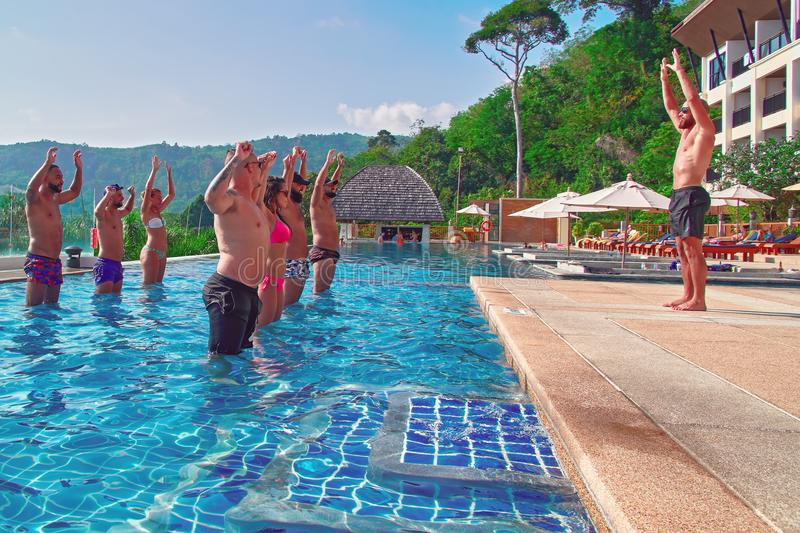 THAILAND, PHUKET, MARCH 23, 2018 - concept crossfit training. Beautiful young guys and girls are engaged crossfit in outdoor pool. royalty free stock photo