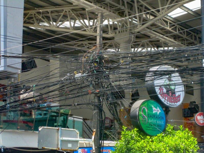 THAILAND PHUKET - MARS 26, 2012: Kaos av kablar och trådar på en elektrisk pol Tråd- och kabelröra fotografering för bildbyråer