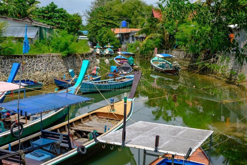 thailand Phuket - 01/05/18 Traditionella träbarkasser av fiskare som blir på ankaret i kanal arkivfoto