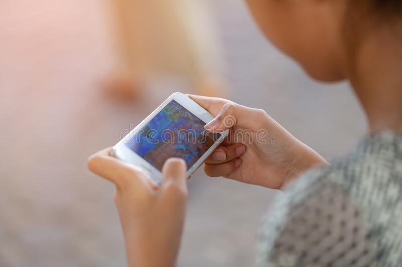 THAILAND, Rayong - April 20, 2019 girl playing Garena RoV Mobile MOBA game in park. technology, education and lifestyle concept stock image