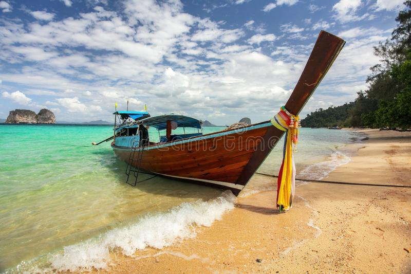 Thailand typical Long-tail boat on clear azure green sea, sky with small clouds above, golden beach on right, Koh Kradan stock image