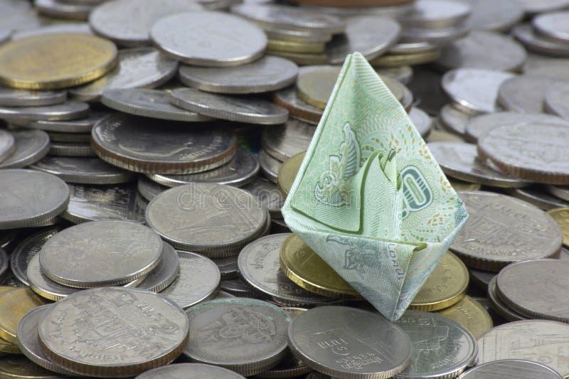 Thailand-Währungsmünzen und -rechnung gefaltet zu den Schiffen Origamikunst Geld von Thailand stockfotos