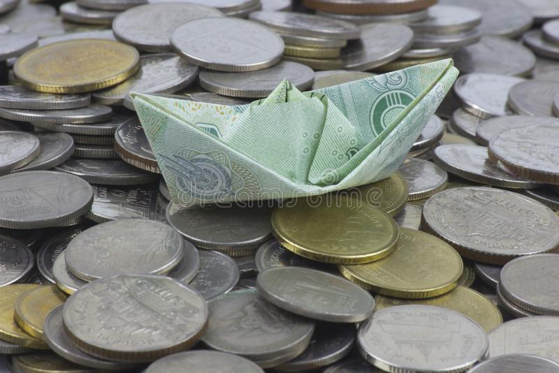 Thailand-Währungsmünzen und -rechnung gefaltet zu den Schiffen Origamikunst Geld von Thailand lizenzfreies stockfoto